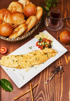 Frühstückssnackkrepps, omletten mit gemüsesalat und brotbrötchen in der weißen platte