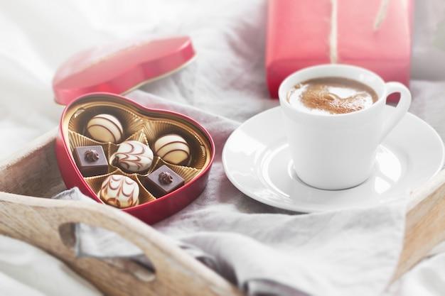 Frühstückstablett mit einem geschenk, blumen und pralinen