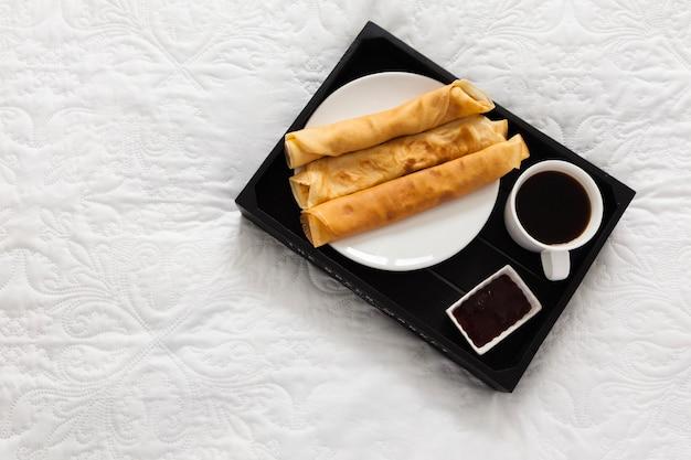 Frühstückstablett mit kaffee, pfannkuchen und sirup