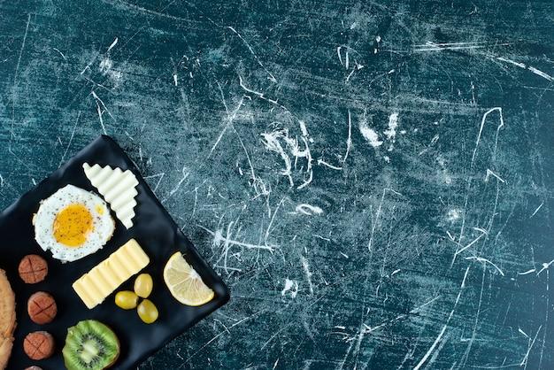 Frühstücksteller mit crpes, spiegelei und beilagen. foto in hoher qualität