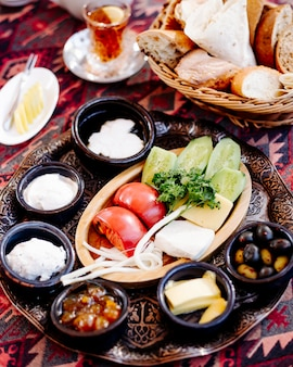 Frühstücksteller mit gemischten speisen, brot und einem glas tee.