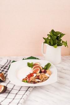 Frühstücksteller mit krug tadellosen blättern und küchenserviette auf weißem marmor