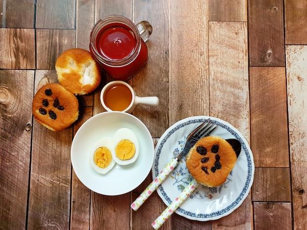 Frühstückstisch kochen sie ei rosinen und kokos-muffin-fruchtsaft-honig auf holzuntergrund