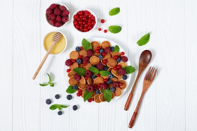 Frühstückstisch mini pfannkuchen beeren minze blätter und honig von oben
