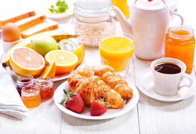 Frühstückstisch mit croissants, kaffee, orangensaft, toast und obst
