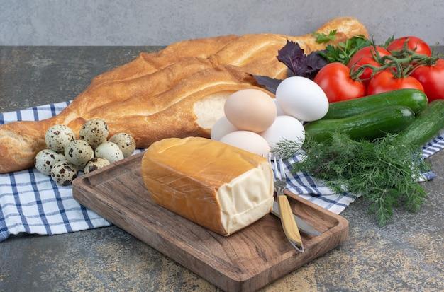 Frühstückstisch mit gemüse, brot, eiern und käse.
