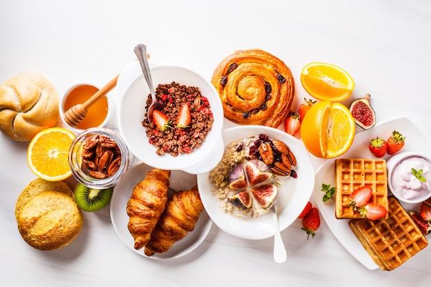 Frühstückstisch mit haferflocken, waffeln, croissants und früchten.