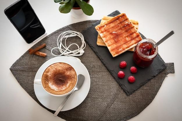 Frühstückstisch mit marmelade und brot und heißem kaffee-cappuccino - arbeitsplatz von zu hause aus