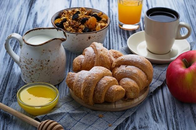 Frühstückstisch mit müsli, croissants, apfel, kaffee, saft.