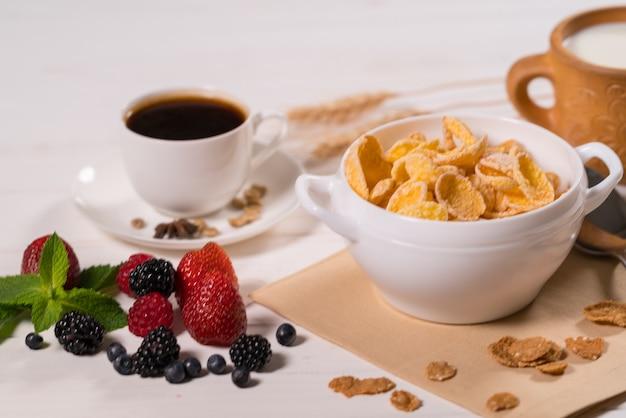 Frühstückstisch mit müsli, tasse kaffee, erdbeeren, brombeeren und blaubeeren
