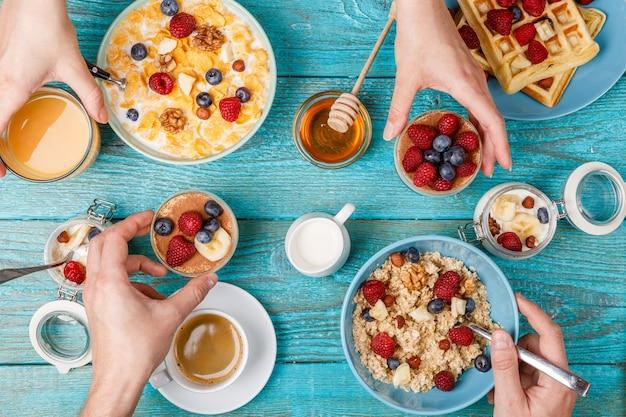 Frühstückstisch mit waffeln, haferflocken, müsli, kaffee, saft und frischen beeren. gesundes frühstück
