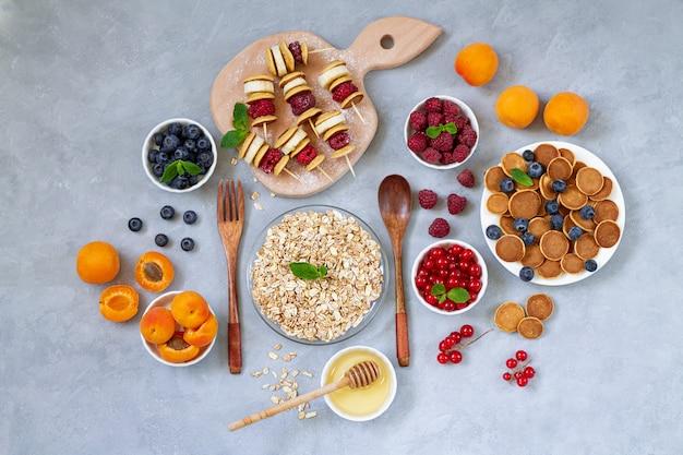 Frühstückstisch pfannkuchen beeren sommerfrüchte pfannkuchen spieße honig und haferflocken draufsicht