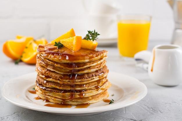 Frühstückstisch. pfannkuchen mit orangen- und ahornsirup, orangensaft und kaffee