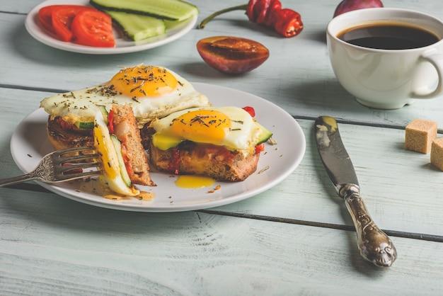 Frühstückstoast mit gemüse und spiegelei auf weißem teller, tasse kaffee und einigen früchten über hölzernem hintergrund. sauberes essen lebensmittelkonzept.