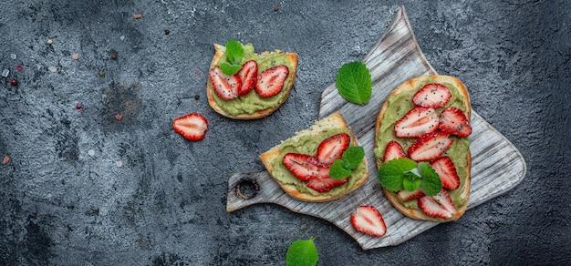Frühstückstoast mit guacamole, erdbeeren und chiasamen