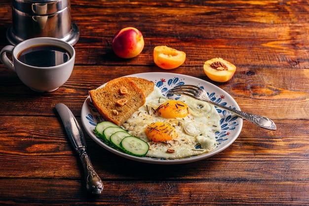 Frühstückstoast mit spiegeleiern mit gemüse auf teller und tasse kaffee mit früchten über dunklem holz
