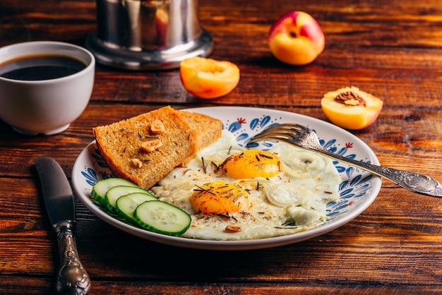 Frühstückstoast mit spiegeleiern mit gemüse auf teller und tasse kaffee mit früchten über dunklem holztisch