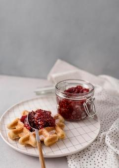 Frühstückswaffeln und himbeermarmelade im glas