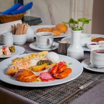 Frühstückswürste von der seite, gekochtes ei, omelett, croissant in tellern und eine tasse tee auf dem tisch