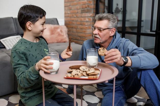 Frühstückszeit, großvater und enkel beim morgenfrühstück mit milch und keksen.
