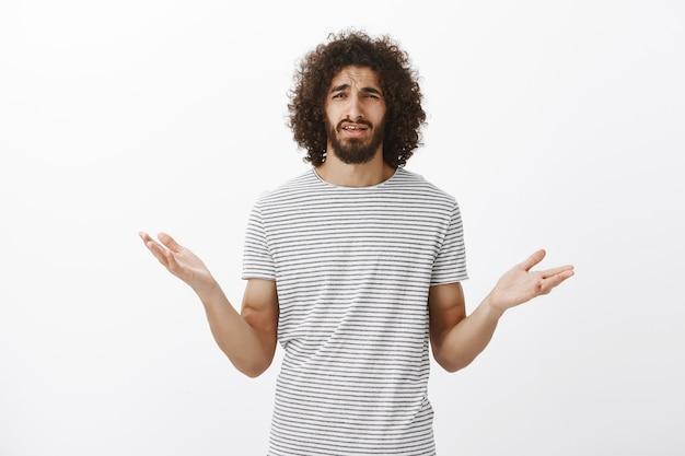Frustriert befragter gutaussehender mann mit bart und lockigem haar, hände ahnungslos gespreizt