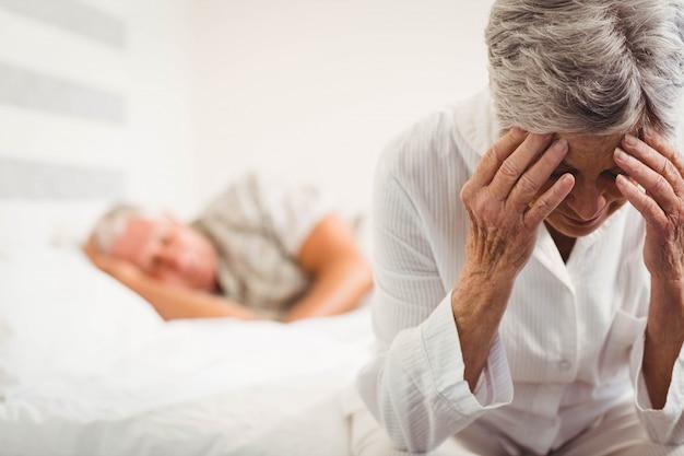 Frustrierte ältere frau, die auf bett im schlafzimmer sitzt
