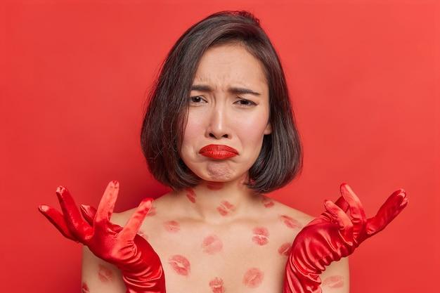 Frustrierte asiatische frau hat einen depressiven ausdruck, sieht traurig aus, breitet sich die hände aus, fühlt sich sehr verärgert wegen problemen