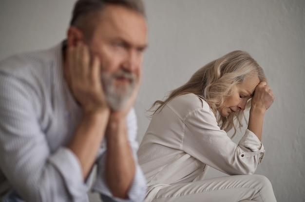 Frustrierte blonde dame und ein stiller grauhaariger mann sitzen getrennt voneinander auf dem bett