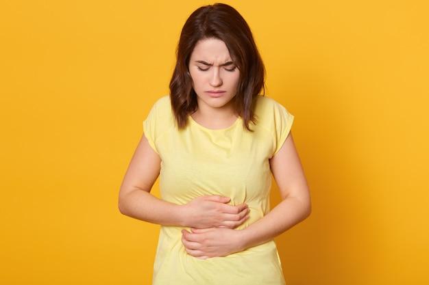 Frustrierte brünette frau, die hände auf bauch hält, fühlt schmerzen wie menstruation oder krankheit, trägt lässiges t-shirt, bleibt zu hause