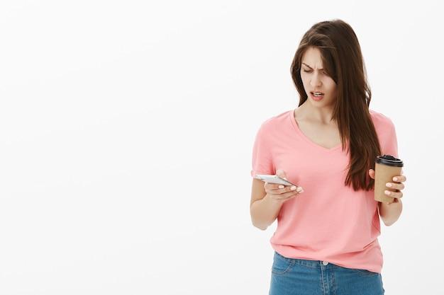 Frustrierte brünette frau, die im studio mit ihrem telefon und kaffee aufwirft