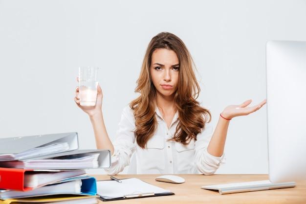 Frustrierte enttäuschte geschäftsfrau, die am schreibtisch im büro sitzt und wasserglas auf weißem hintergrund hält