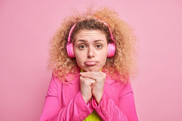 Frustrierte europäische frau hält hände unter kinntaschen lippen sieht mit traurigem ausdruck aus hört musik über kopfhörer in hellen kleidern gekleidet hat schlechte laune isoliert über rosa wand