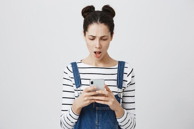 Frustrierte frau, die nachricht auf smartphone liest