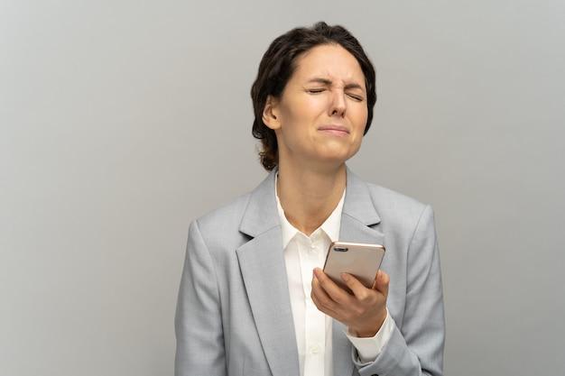 Frustrierte frau hält telefon weinen, betäubt von schlechten negativen nachrichten disziplinarmaßnahmen und entlassung