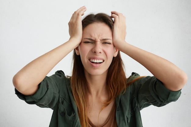 Frustrierte frau mit schrecklichen kopfschmerzen, die hände auf dem kopf halten und ihr gesicht mit schmerzen runzeln, die unglücklich und stressig aussehen. hausfrau in der verzweiflung, die stressige situation in ihrem leben leidet