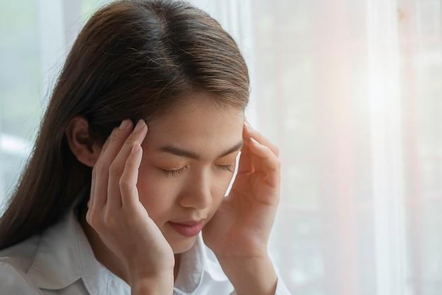 Frustrierte geschäftsfrau, die unter kopfschmerzen leidet