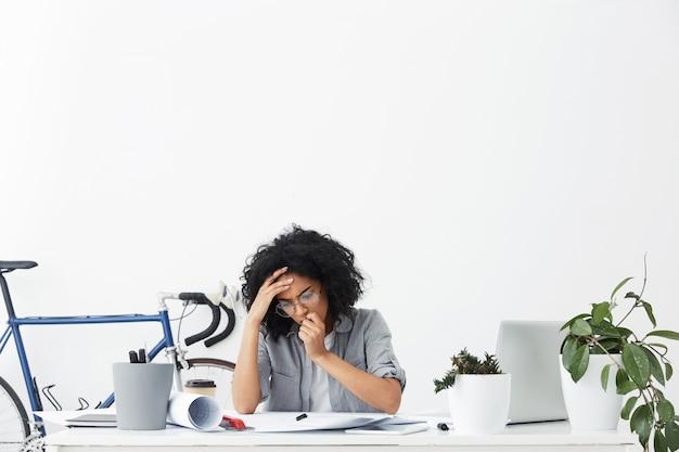 Frustrierte ingenieurin, die ihre technischen zeichnungen überprüft