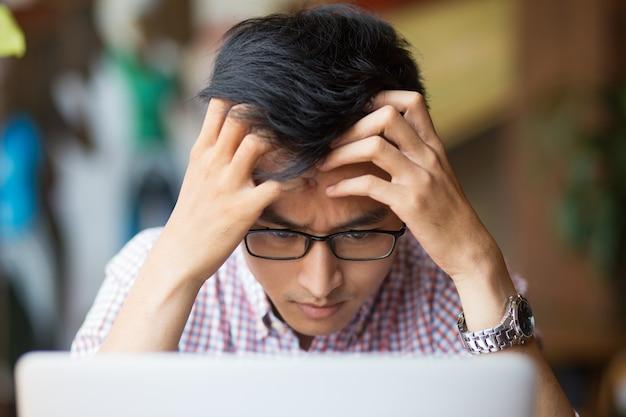 Frustrierte junge asiatische mann sitzt am laptop