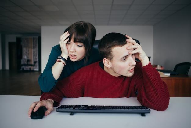 Frustrierte junge büroangestellte in der nähe des computers. emotional schöne junge leute am arbeitsplatz.