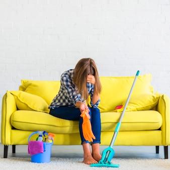 Frustrierte junge frau, die auf sofa mit reinigungsausrüstungen sitzt