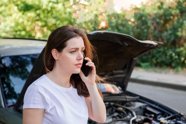Frustrierte junge frau, die handy um hilfe anruft versicherungskrankenwagen nach autounfall