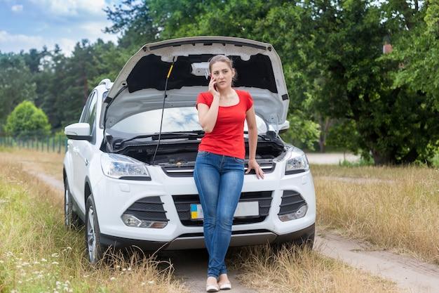 Frustrierte junge frau, die sich auf dem feld auf ein kaputtes auto stützt und auf dem handy um hilfe ruft