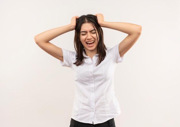 Frustrierte junge frau im weißen hemd, das wild geht, indem sie ihr haar zieht, das über weißer wand steht