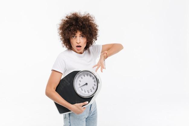 Frustrierte junge lässige frau, die auf gewichte zeigt