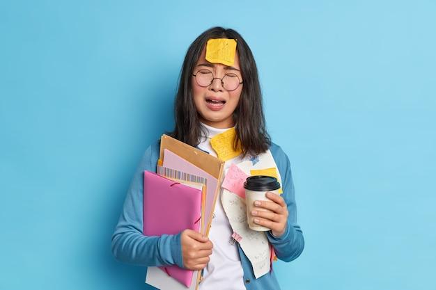 Frustrierte müde marketing-expertin trägt papiere mit dokumenten, trägt haftnotizen mit den notwendigen informationen, um sich an müdigkeit zu erinnern, weil job aus der ferne kaffee zum mitnehmen trinkt