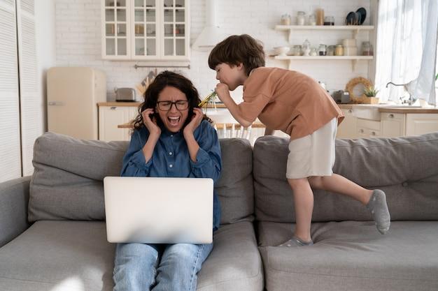 Frustrierte mutter eines hyperaktiven kindes schreit nach nerviger chaosarbeit am laptop mit ungehorsamem sohn