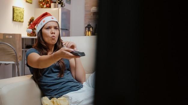 Frustrierte person wechselt die kanäle im fernsehen mit der fernbedienung
