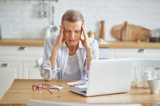Frustrierte reife frau, die unter kopfschmerzen leidet, während sie von zu hause aus online arbeitet