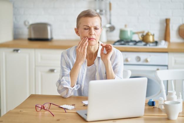 Frustrierte reife frau, die unter zahnschmerzen leidet, während sie von zu hause aus online arbeitet