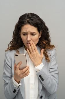 Frustrierte schockierte geschäftsfrau oder büroangestellte, die telefon betrachten, betäubt mit schlechten negativen nachrichten